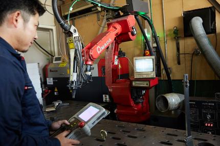 ロボット溶接機を操作する男性の写真